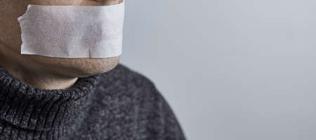 Horizontal shot of man silenced with duct tape over his mouth. Photo with copy space.