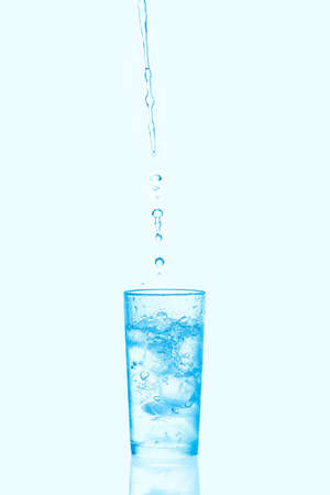 Vertical shot of pouring water into glass with ice isolated on blue background.
