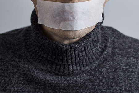 Horizontal shot of man silenced with duct tape over his mouth.