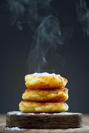 Vertical shot of hot pancakes on a wooden plate sprinkled with powdered sugar on a dark background. Steam rises from the pancakes.