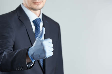 Horizontal shot of businessman in rubber gloves gives a thumbs up. Crop photo with copy space. 写真素材