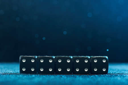 Horizontal shot of five identical black dice on a blue background. The concept of gambling. Photo with bokeh.