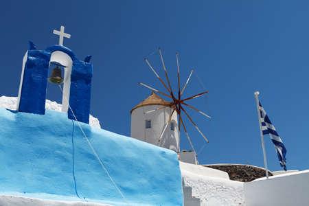 Flag, windmill and belfry on Santorini island, Greece Stock Photo