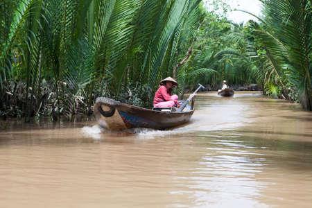 freshwater sailor: VIETNAM - OCT 19: Vietnamese woman rowing a boat in Mekong River on October 19, 2013, in Saigon Vietnam. Editorial