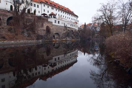 headquaters: Old Jesuit dormitory in Cesky Krumlov reflected in Vltava river. Bohemia, Czech republic Stock Photo
