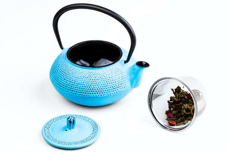 tetsubin: blue pig-iron teapot and stainless-steel infuser with green tea isolated on white background