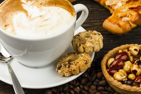 cup of cappucino and cakes on dark background photo