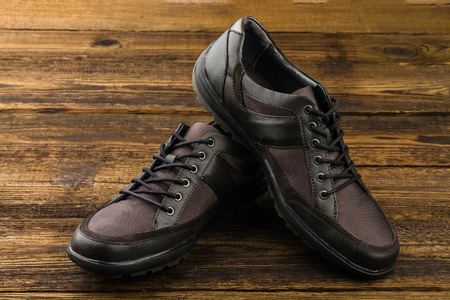 rubber lining: combined mans shoes on wooden background