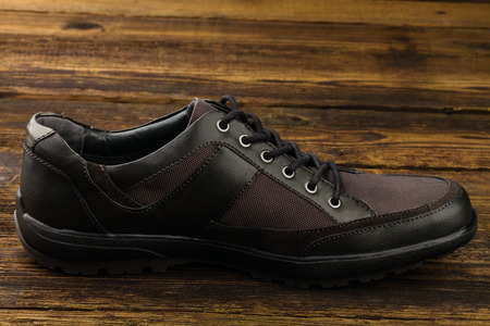 rubber lining: combined  mans shoe on wooden background