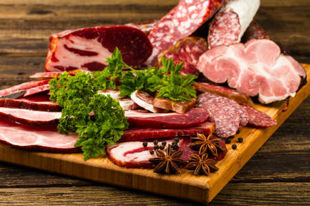 sausage, meat, vegetables and spices on wooden background photo