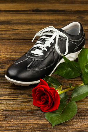 rubber lining: black mans shoe and rose on wooden background Stock Photo
