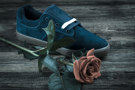 rubber lining: dark blue mans shoe and rose on wooden background Stock Photo