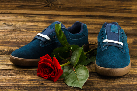 rubber lining: dark blue mans shoes and rose on wooden background Stock Photo