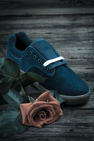 dark blue mans shoe and rose on wooden background photo