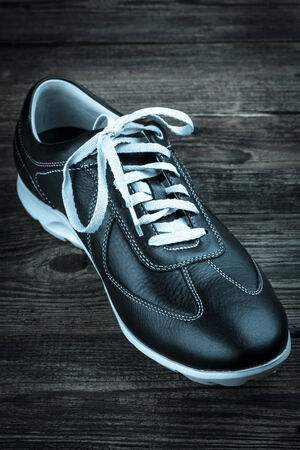 rubber lining: black leather mans shoe on wooden background