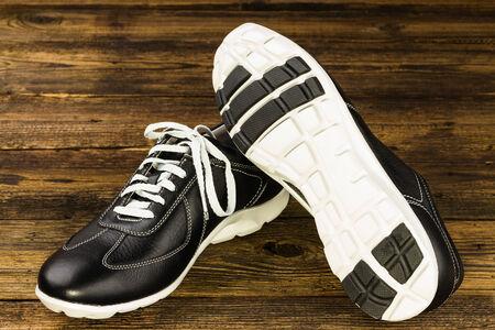 black leather mans shoe on wooden background