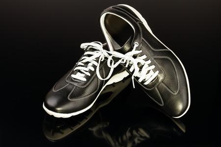 black leather mans shoe on black background photo
