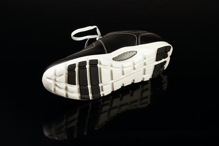 black leather mans shoe on black background