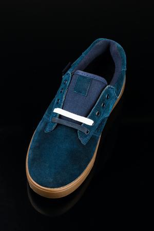 dark blue velvet mans shoe on black background