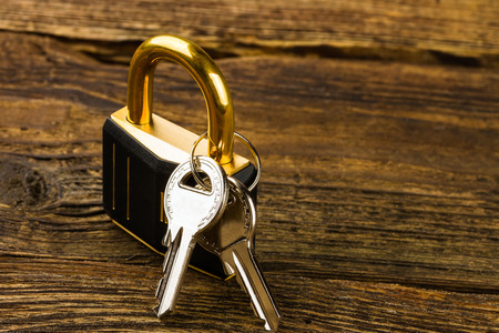 hinged lock with keys on wooden background photo