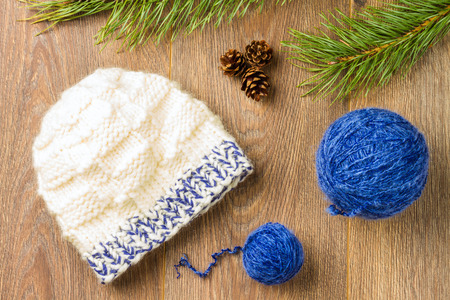 pinecones: ball of threads, knitting cap, pine-cones and branch of  pine on wooden background