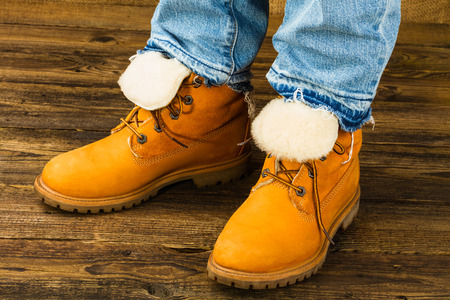 rubber lining: female feet in winter boots and jeans  on wooden background