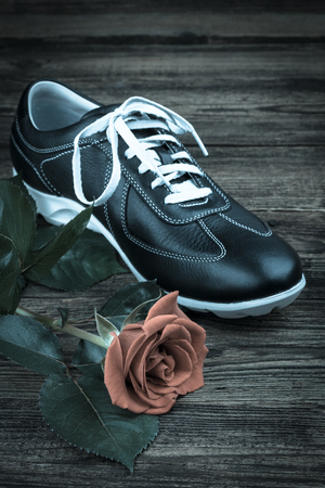 rubber lining: Black mans shoe and rose on wooden