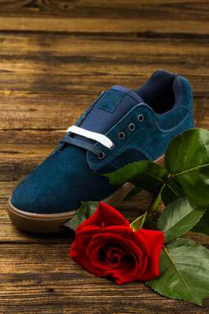 rubber lining: Dark blue mans shoe and rose on wooden
