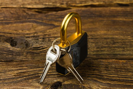 hinged: hinged lock with keys on wooden background