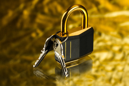 doorlock: hinged lock with keys on golden background Stock Photo