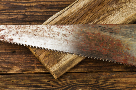 hacksaw: hacksaw and board on wooden background