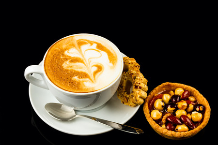 cappucino: cup of cappucino and cakes on black background Stock Photo
