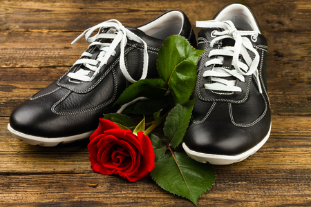 black mans shoes and rose on wooden background