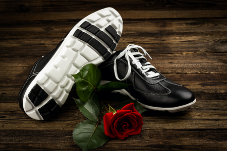 rubber lining: black mans shoes and rose on wooden background