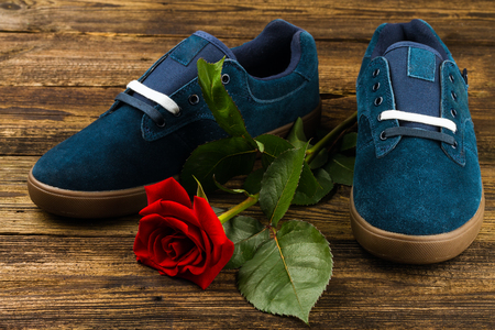 wonderfull: dark blue mans shoes and rose on wooden background Stock Photo