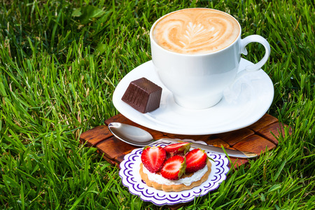 cappucino: Cup of cappucino and sweet dessert on grass