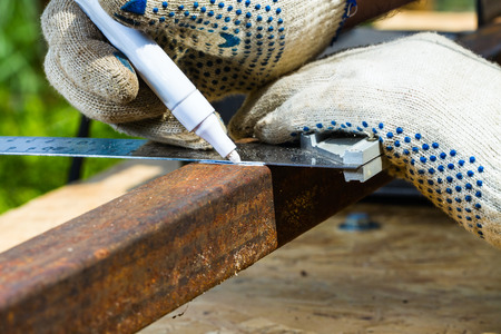 profile measurement: marking rusty metal square pipe for cutting Stock Photo