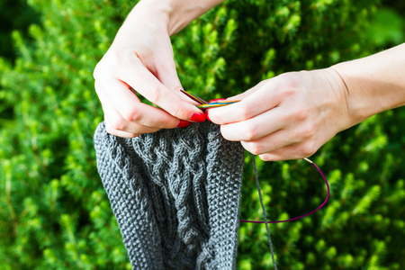 grey nails: handmade woolen scarf and female hands on fir-tree background