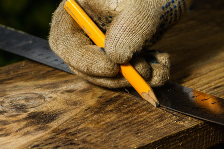 profile measurement: marking pine-tree boards for cutting Stock Photo