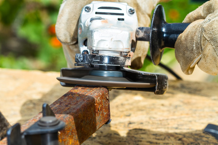 profile measurement: cleaning edge of square pipe by grinding machine with abrasive disk Stock Photo