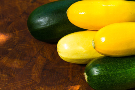 green and yellow vegetable marrow on oak kitchen board