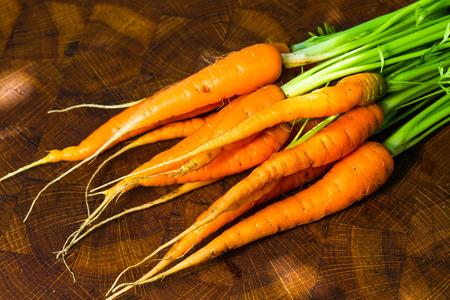 fresh ripe carrots on oak kitchen board Stock Photo