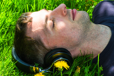 electronical: young man listening music with wireless headphones, lying on the lawn with dandelions Stock Photo