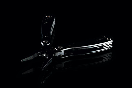 black steel folding multitool on dark background, low-key