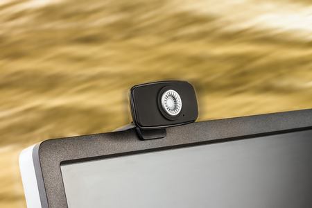 Digital black computer monitor screen and HD web camera on golden background Stock Photo