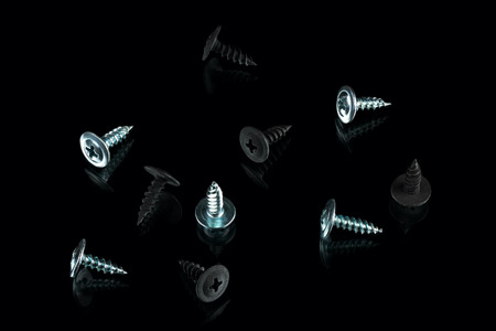 silver chrom and anodized screws on black background Фото со стока