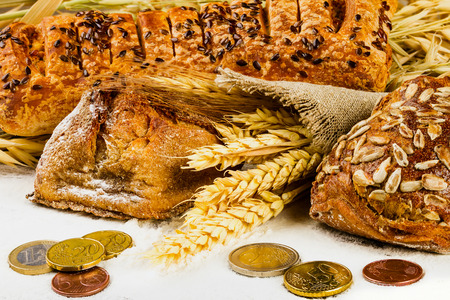 white bread with spikelets of wheat, oats, rye and coins on wooden background with flour Фото со стока