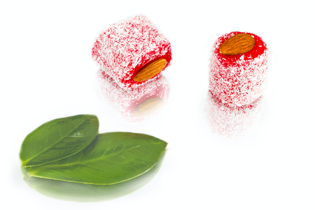 rakhat-lukum sprinkled with coconut shavings and green leaf on white background, turkish sweets Фото со стока
