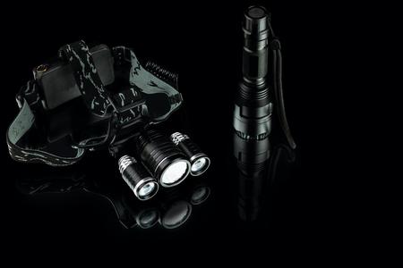 anodized aluminium waterproof tactical flashlight and headlamp on black background