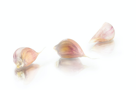 fresh nice garlic cloves with reflection on white background